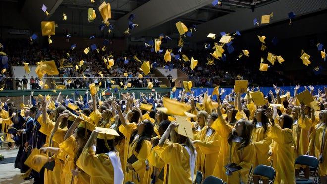 Graduates throw their caps in the air during Port Huron Northern High School's commencement ceremony Wednesday at McMorran Arena.