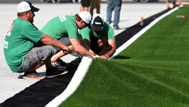 Workers from Sports Construction Management Inc. install turf as the transformation of Bristol Motor Speedway from a NASCAR track to a football stadium continues Wednesday, Aug. 24, 2016, in Bristol, Tenn. The track is being prepared for the Pilot Flying J Battle at Bristol on Sept. 10 when Tennessee and Virginia Tech will play before an anticipated crowd in excess of 150,000, the largest ever to witness a football game.