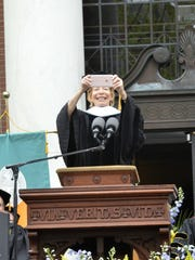 Author and journalist Gail Sheehy holds up her iPhone to snap a picture of the University of Vermont class of 2016 on Sunday during commencement,