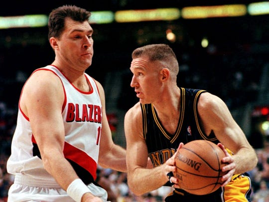 Portland Trail Blazers center Arvydas Sabonis left comes out to defend Indiana Pacers forward Chris Mullin during the first half in Portland Ore. Wednesday Feb. 10 1999.