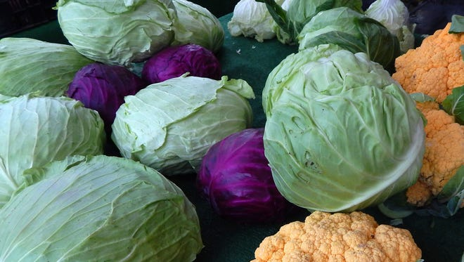 Normal sized red cabbage, in the middle, next to a giant head of green cabbage, at the Xiong Ranch booth at the Westlake Village farmers market. Farmer Vang Xiong says she doesn't do anything special, she only waters her enormous vegetables.