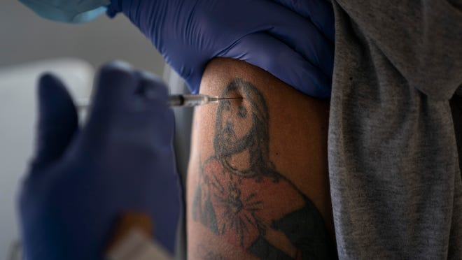 Farm worker Jorge Americano receives a COVID-19 vaccine in his arm, bearing a tattoo depicting Jesus, at Tudor Ranch in Mecca, Calif., on Thursday.