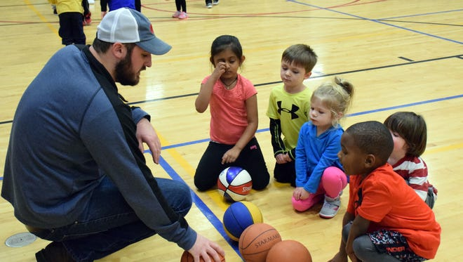 """Volunteer coach Jake Showalter, left, talks with his group of kids about passing during the """"Little Dribblers"""" basketball clinic at the Staunton Area YMCA on Wednesday, Jan. 11, 2017. We"""