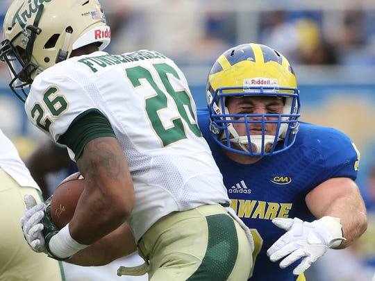 Delaware linebacker Troy Reeder starts a tackle on William and Mary's Albert Funderburke Jr in the first quarter of Delaware's 17-0 win at Delaware Stadium last year.