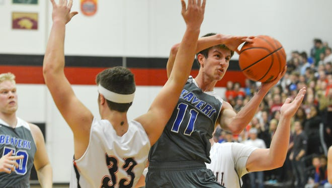 Harper Creek's Jeremiah Davis (11) tries for a layup past Marshall defenders during second quarter of play Friday night.