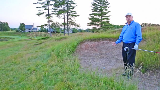 Jim Richerson stands in the infamous Whistling Straits 18th hole fairway bunker that pro golfer Dustin Johnson hit into during the 2010 PGA Championship.