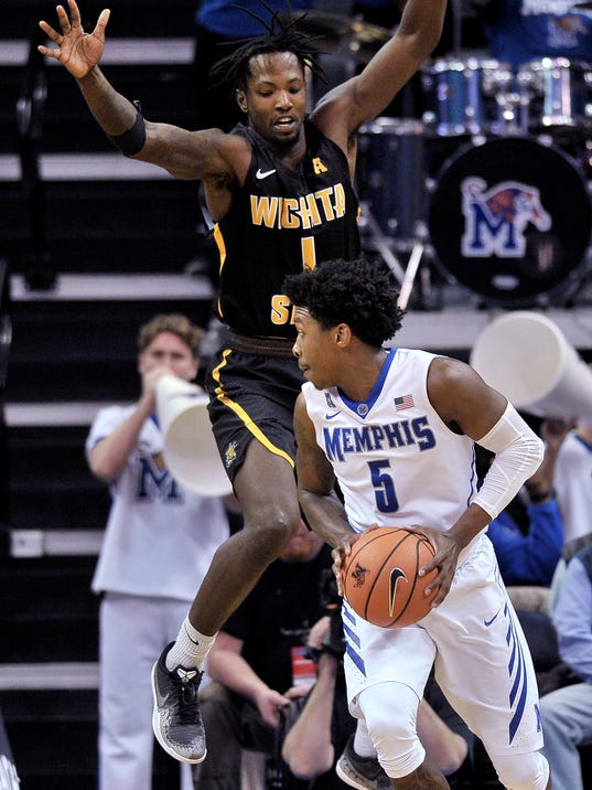 Memphis guard Kareem Brewton Jr. (5) controls the ball against Wichita State forward Zach Brown (1) during the second half of an NCAA college basketball game Tuesday, Feb. 6, 2018, in Memphis, Tenn. (AP Photo/Brandon Dill)