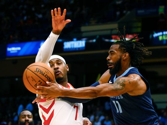 Grizzlies guard Mike Conley (11) is fouled by Rockets forward Carmelo Anthony (7) as he goes up for a shot during the first half Tuesday.