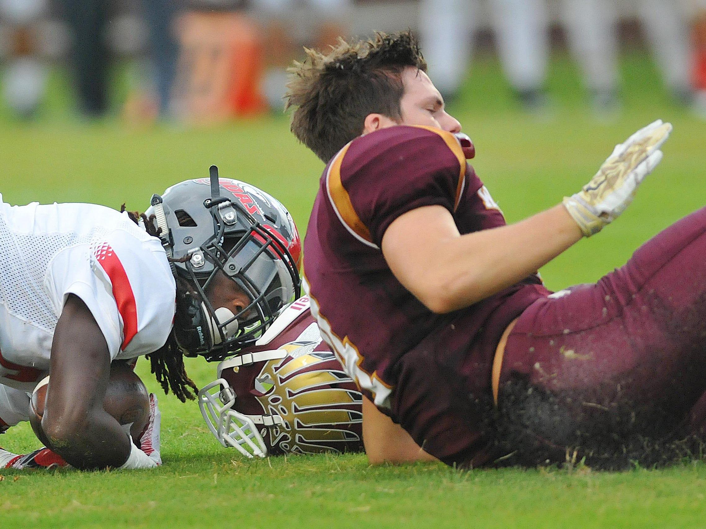 Astronaut high's #4 Cameron Ockerman loses his helmet as he hammers New Smyrna Highs #22 Einaj Carter during Friday nights game held at Storey -Taylor Stadium Astronaut High School.