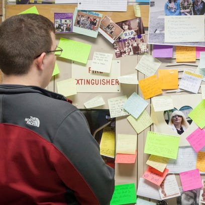 Trenton Reynolds leaves a note on student Allie McKim's