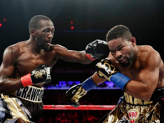 Terence Crawford, left, punches Dominican Republic's Felix Diaz during the second round of a super lightweight championship boxing match Saturday, May 20, 2017, in New York. Crawford won after the fight was stopped after the 10th round. (AP Photo/Frank Franklin II)
