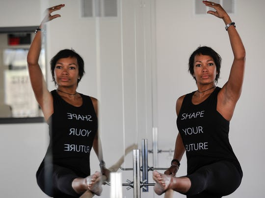 Kimberly Lewis owner of Cardio Barre poses before class