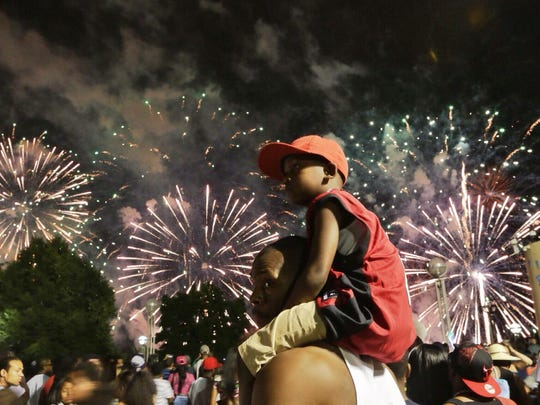 Donald Readous Jr. of Detroit watches, sitting on his father Donald Readous' shoulders at Hart Plaza during last year's fireworks. This year's show is supposed to be one minute longer.