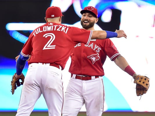Toronto Blue Jays shortstop Troy Tulowitzki (2) and center fielder Kevin Pillar celebrate after defeating the New York Yankees in baseball game action in Toronto, Sunday, June 4, 2017. (Frank Gunn/The Canadian Press via AP)