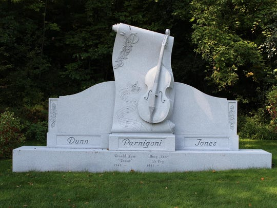 This monument at Hope Cemetery has a musical instrument and musical notes.
