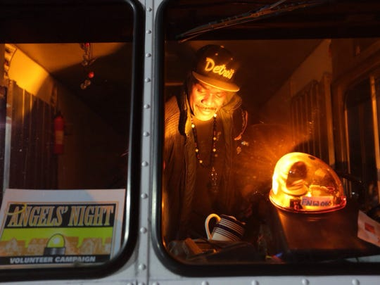 Duane Jones, 54, of Detroit puts a yellow light on the dash of his vehicle while preparing to patrol a neighborhood during Angels' Night at the Northwest Activities Center in Detroit in 2017.