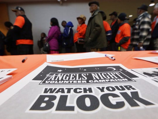 Volunteers wait in line for food after patrolling neighborhoods during Angels' Night at the Northwest Activities Center in Detroit on Thursday.