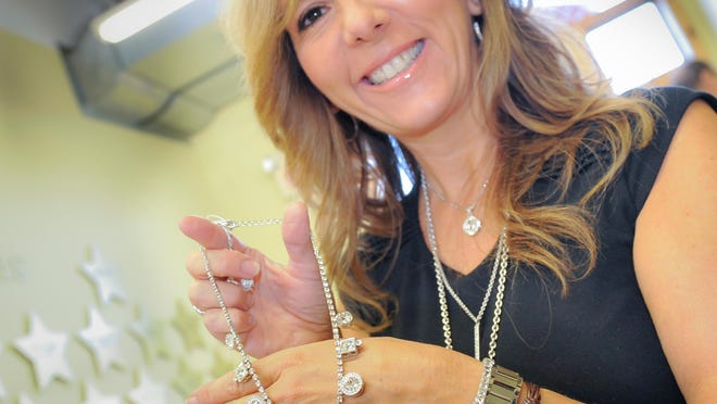 Laura D'Urso, who sells Touchstone Crystal by Swarovski jewelry, displays a Spotlight Collar Crystal Necklace.