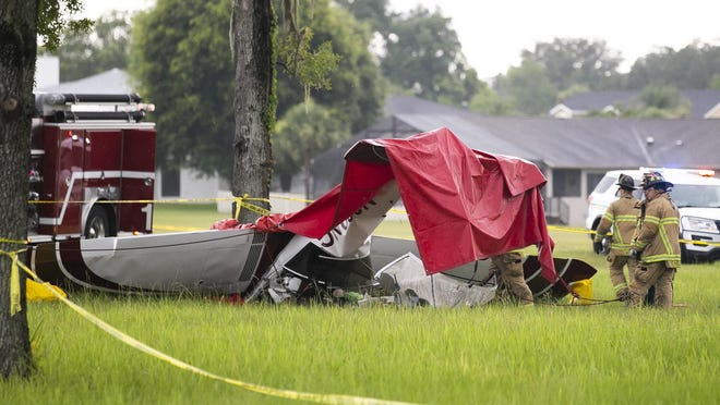 Marion County Fire Rescue firefighters work the scene of a fatal plane crash on Wednesday at Leeward Air Ranch near Ocala. The pilot, who was the only person aboard, was killed when her single-engine craft crashed while coming in for a landing.