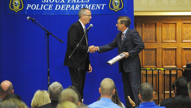 Sioux Falls Mayor Mike Huether shakes hands with Sioux Falls Police Chief Doug Barthel during a retirement celebration for Barthel on Friday at the Multi-Cultural Center in Sioux Falls.
