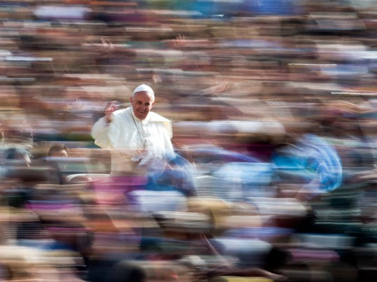 Pope Francis waves to the crowd as he arrives on his