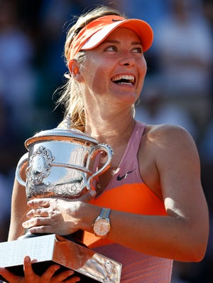 Sharapova holds the trophy as she poses during the ceremony after defeating Simona Halep.