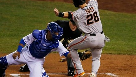 Home plate umpire Jerry Meals watches as San Francisco Giants' Buster Posey is tagged out by Kansas City Royals catcher Salvador Perez during the first inning of Game 1 of baseball's World Series Tuesday, Oct. 21, 2014, in Kansas City, Mo. Posey tried to score from second on a hit by Pablo Sandoval. (AP Photo/Orlin Wagner)