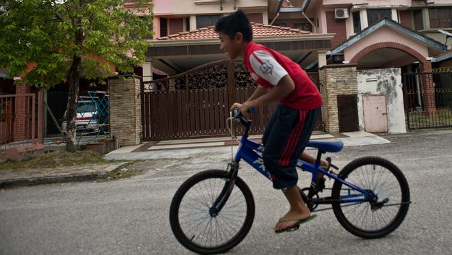 A Malaysian boy rides his bicycle past the home of missing Malaysia Airlines Flight 370 pilot Zahari Ahmad Shah in Shah Alam, outside Kuala Lumpur on March 16, 2014.  The pilot's son told the New Strait Times newspaper of Malaysia that he is ignoring speculation about his father's role in the loss of the aircraft andn all aboard.