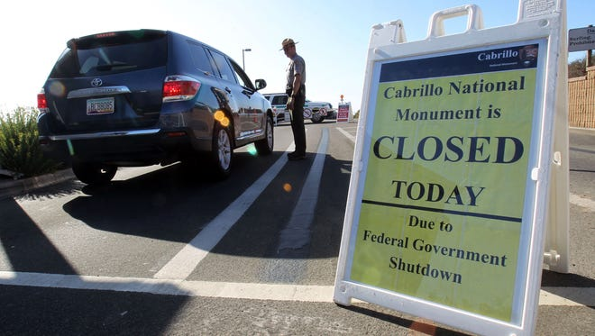 Chief law enforcement ranger Ralph Jones advises visitors to Cabrillo National Monument that the park is closed on Tuesday in San Diego, Calif., on the first day of of the government shutdown.
