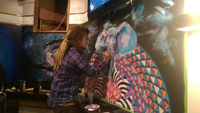 An artist paints his mural at the Hoffman House's new Canvas Lounge.