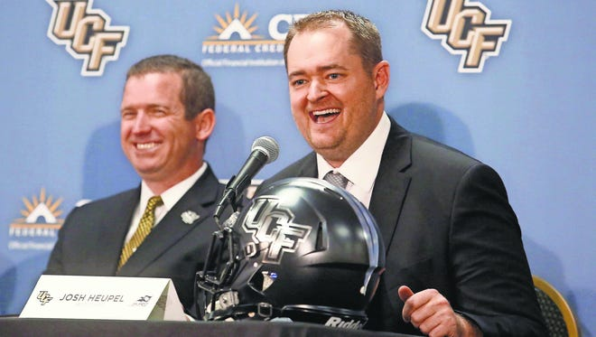 Josh Heupel, right, is introduced as the new Central Florida head football coach by Danny White, UCF Athletic director in Orlando, Fla., Tuesday, Dec. 5, 2017. Heupel has been the offensive coordinator at Missouri the past two seasons. He replaces Scott Frost, who accepted the Nebraska coaching job after leading UCF to a 12-0 record and the American Athletic Conference title.