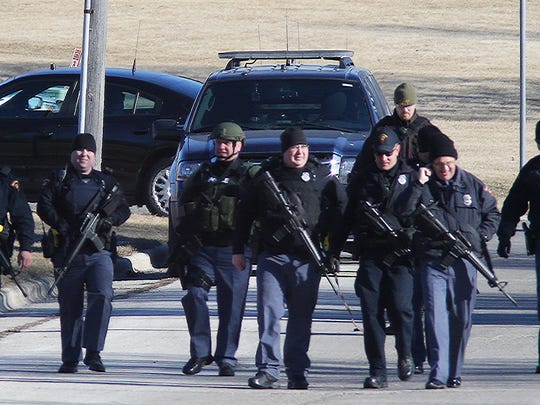 Armed police patrol a street near Kiel High School following reports of shots fired, Friday, March 23, 2018, in KIel, Wis. School was cancelled after shots were heard by a staff member at the high school before classes started at Kiel.