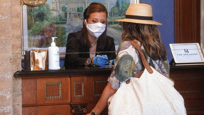 A member of The Breakers guest relations team helps a guest check into the hotel which reopened on Friday after being closed due to the coronavirus pandemic, May 22, 2020.