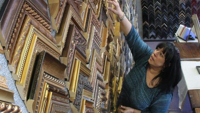 Dana Parisi works in her Shrewsbury shop, The Finicky Framer.