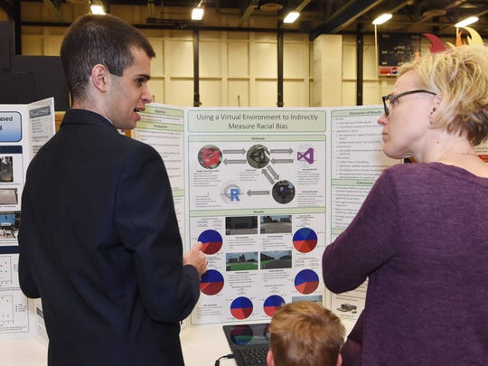 Daniel Busaba, 17, left, a student at Spackenkill High School, discusses his science fair project with Dawn Essig, right, of Salt Point at the Dutchess County Regional Science Fair, held at Dutchess County Community College in the Town of Poughkeepsie.