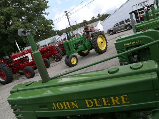 Bill and Cathy Gardener ride a 1944 John Deere Model A through the Buckeye Iron Will Club exhibit at the Richland County Fairgrounds on Saturday.