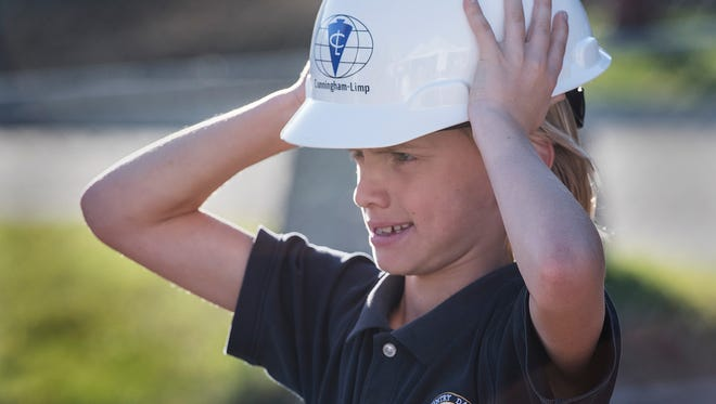 Sawyer Shilling tries on a hard hat after the ceremony.