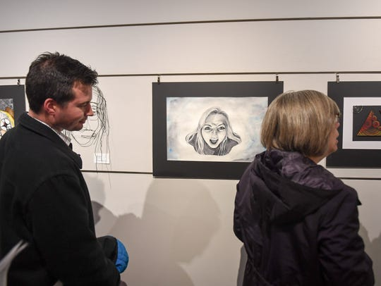 Parents and students look over art exhibits at the