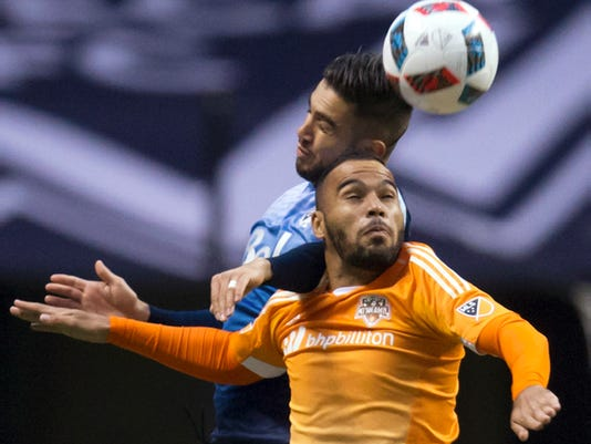 Houston Dynamo's Alex Monteiro de Lima, front, and Vancouver Whitecaps' Pedro Morales vie for the ball during the first half of an MLS soccer game in Vancouver, British Columbia, on Saturday, March 26, 2016. (Darryl Dyck/The Canadian Press via AP)