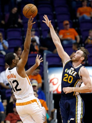 The Suns' T.J. Warren shoots over Utah's Gordon Hayward during an NBA preseason game on Friday, Oct. 9, 2015, in Phoenix. The Suns defeated the Jazz 101-85.