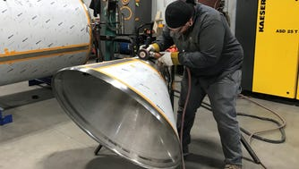 Troy Kasmar works on part of a brewery tank for Quality Tank Solutions