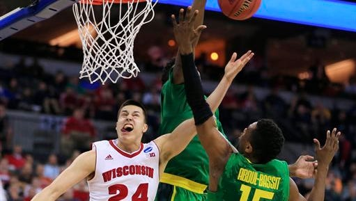 Oregon's Jordan Bell, rear, blocks a shot by Wisconsin's Bronson Koenig (24), with Oregon's Jalil Abdul-Bassit (15) defending, during the second half of an NCAA tournament college basketball game in the Round of 32 in Omaha, Neb., Sunday, March 22, 2015.