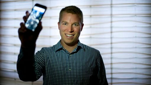 In this Friday, June 5, 2015 photo, Dan Estes, a Los Angeles real estate broker, pauses for photos with his smartphone showing the app that he built to record the time and place where he sees waste in Los Angeles. (AP Photo/Jae C. Hong)