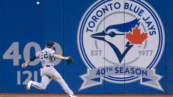New York Yankees centrt fielder Jacooby Ellsbury chases down a double by Toronto Blue Jays' Jose Bautista during the third inning of a baseball game Tuesday, April 12, 2016, in Toronto.
