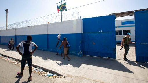 In this Aug. 16, 2016 photo, a Brazilian U.N. peacekeeper opens a gate at the U.N. base in the Cite Soleil slum of Port-au-Prince, Haiti. According to an AP investigation, some 150 allegations of abuse and exploitation were reported in Haiti between 2004 and 2016. The allegations involved U.N. peacekeepers and other personnel. Alleged victimizers came from Bangladesh, Brazil, Jordan, Nigeria, Pakistan, Uruguay and Sri Lanka, according to U.N. data and interviews. More countries may have been involved, but the United Nations only started disclosing alleged perpetrators' nationalities after 2015.