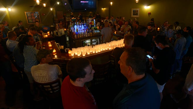 Lit candles adourn the bar Sunday in preparatition for the Candlelight Vigil at Emerald City to show support for the victims of the killings at the Pulse nightclub in Orlando.