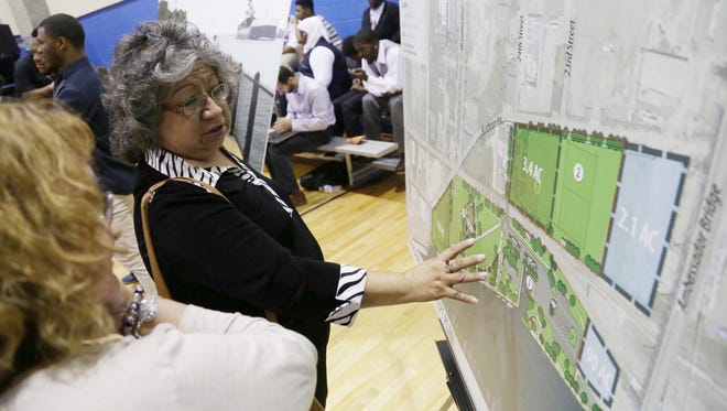 Detroit residents Erminia Ramirez (left) and Alicia Juarez look over concept plans for Riverside Park they support during a community meeting at the Latin Americans for Social Economic Development gym in Detroit on Thursday June 25, 2015 to discuss the city's deal to swap land with Moroun's company Detroit International Bridge Co.