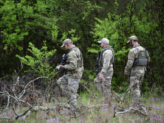 ATF personnel search a wooded area Monday, April 23,