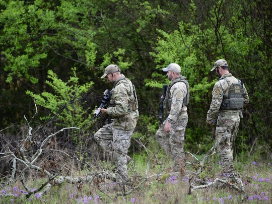 ATF personnel search a wooded area Monday, April 23, 2018 near the Church of Christ Burnette Chapel, scene of the 2017 Antioch church shooting, for the gunman who shot and killed four people early Sunday morning in a nearby Waffle House in Nashville, Tenn. The suspect is still at large.