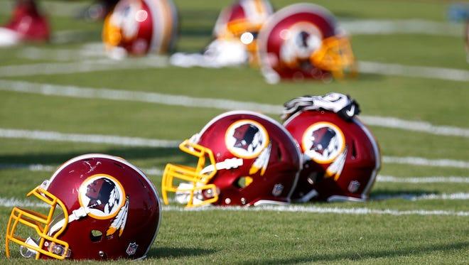 Washington Redskins helmets rest on the field during minicamp at Redskins Park.